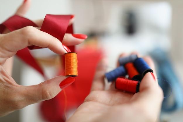 Яркие нитки для шитья лежат на ладони швеи под цвет швеи.