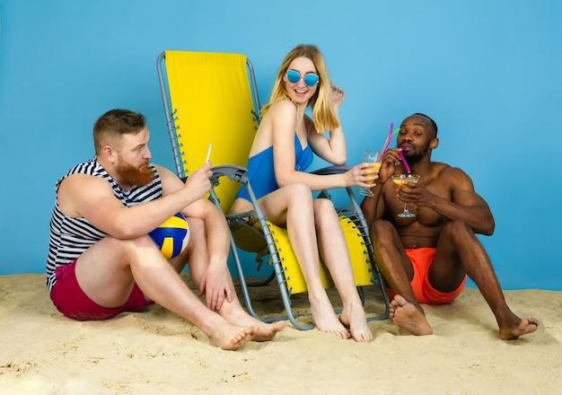 Tempo luminoso. amici felici che riposano, bevendo cocktail su sfondo blu studio. concetto di emozioni umane, espressione facciale, vacanze estive o fine settimana. freddo, estate, mare, oceano, alcol.