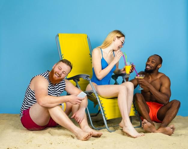明るい時間。青いスタジオの背景にカクテルを飲みながら休んで幸せな友達。人間の感情、顔の表情、夏休みや週末の概念。寒さ、夏、海、海、アルコール。