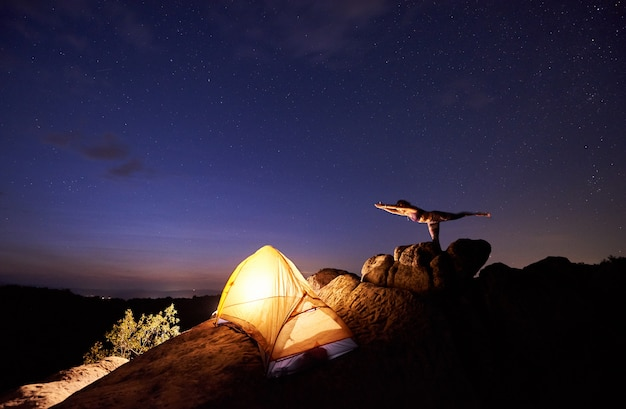 Bright tourist tent on steep rock and young slim woman doing gymnastic yoga exercises against blue starry evening sky