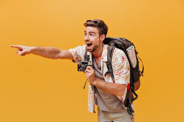 白いクールなシャツと灰色のtシャツで生姜のひげを持った明るい観光客が指を脇に置き、孤立した壁にカメラを持っています