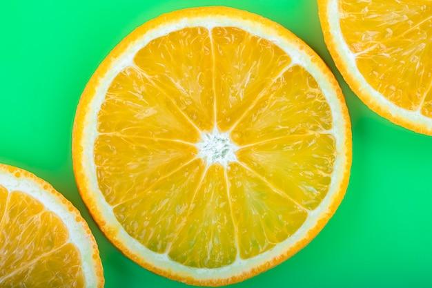 녹색 배경에 오렌지 과일 근접 촬영으로 밝은 열 대 여름 패턴입니다.