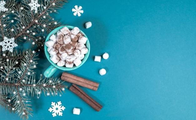 Яркий бирюзовый новогодний фон с еловыми ветками со снегом и чашкой кофе или какао с зефиром. уютный домашний праздник. рождественские украшения. вид сверху, плоская планировка. скопируйте место для текста.