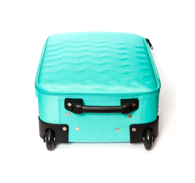 Bright turquoise travel suitcase isolated on white