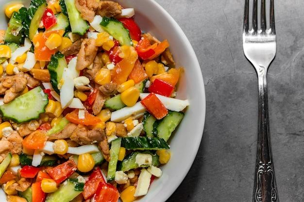 灰色のコンクリートの背景に鶏肉と明るい野菜のサラダ。健康的な食生活のためのおいしいサラダを作る。ボウルとフォークで適切な栄養をとるための野菜サラダ