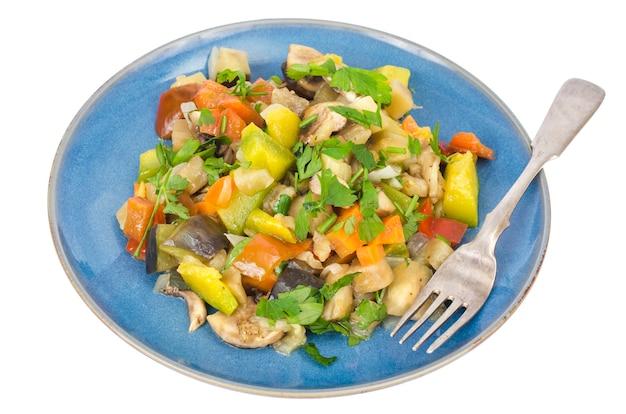 白い背景のプレートに季節の野菜の明るい野菜シチュー。