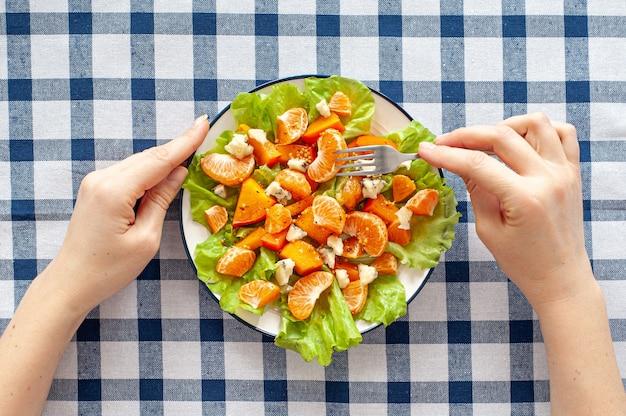 柿、みかん、ブルーチーズの市松模様のテーブルクロスに鮮やかなビタミンサラダ。女性の手はフォークとサラダのプレートを持っています。食事療法のビタミン食品。上からの眺め。