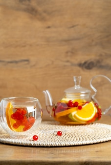 Bright vitamin tea with fruit in a glass teapot cup on the kitchen table on a wooden background