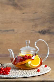 Bright vitamin tea with fruit in a glass teapot on the table on a wooden background closeup