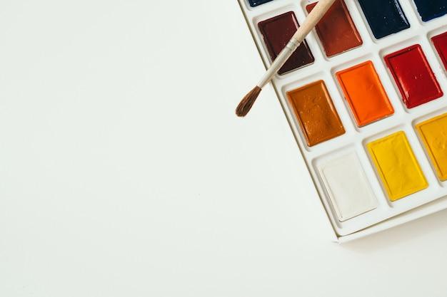Яркие акварельные краски на белом фоне место для текста кисть ложится рядом с красками ...