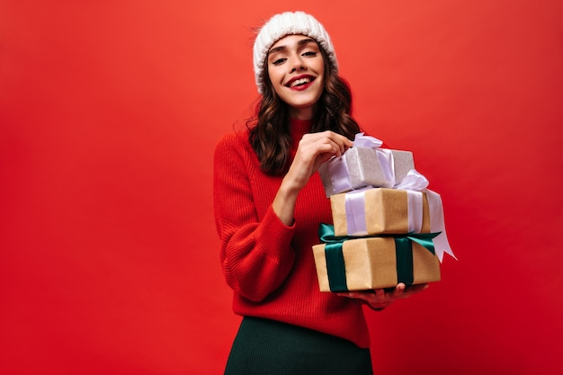 Bright wavy haired girl in sweater and light cap holding gift boxes on isolated wall