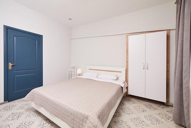 더블 침대와 옷장이있는 밝은 흰색 침실 인테리어. 실제 사진. 실제 사진. 사람이 없습니다.