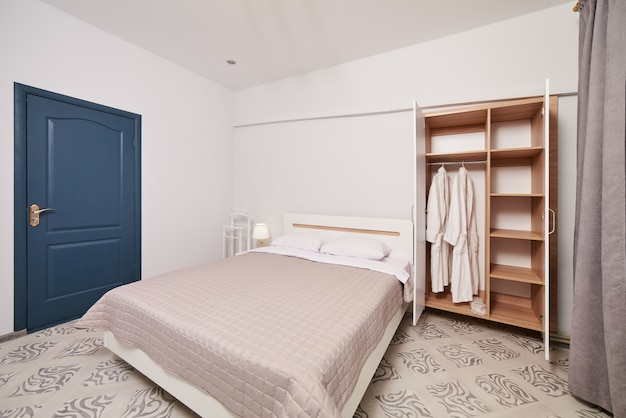 Bright white bedroom interior with double bed and open wardrobe with two white robes.