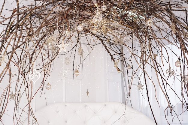 Bright white room with canopy of branches - christmas decoration at home