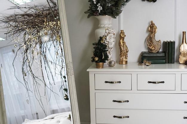 Ярко-белая комната с зеркалом и балдахином из веток - новогоднее украшение дома