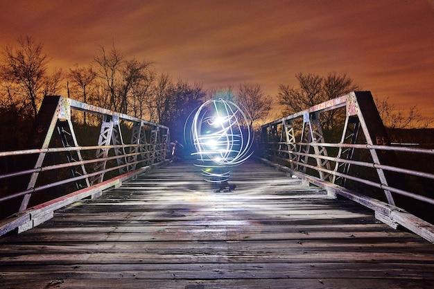 Bright white sphere of light illuminates a white bridge at twilight