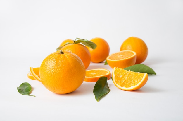 Bright whole oranges with green leaves and cut fruits