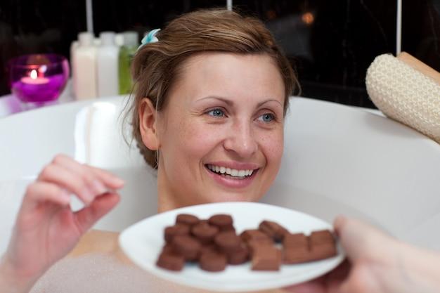 Bright woman eating chocolate while having a bath
