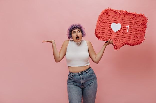軽い服装でピアスをしている明るい女性は驚いています。ピンクでポーズをとって紫色の髪のかわいい女性