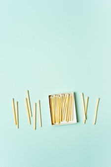 Bright wooden matches scattered from matchbox on a turquoise pastel color background