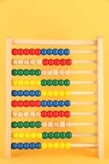 Яркие деревянные игрушки счеты, на желтом фоне