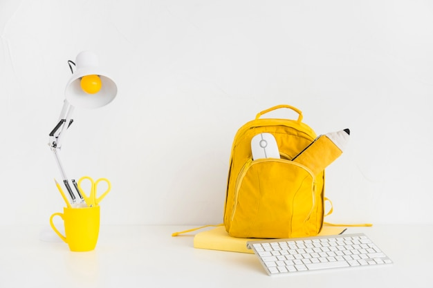Bright workspace with yellow backpack and keyboard