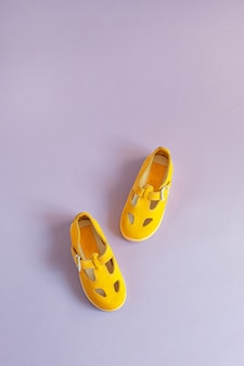 Bright yellow baby shoes on a lilac background with copyspace