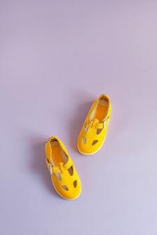 Ярко-желтая детская обувь на сиреневом фоне с copyspace