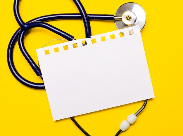 On a bright yellow background, a blue stethoscope and a sheet of paper with a place to insert text. medical concept