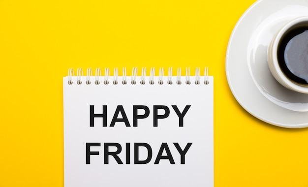 On a bright yellow background, a white cup with coffee and a white notepad with the words happy friday