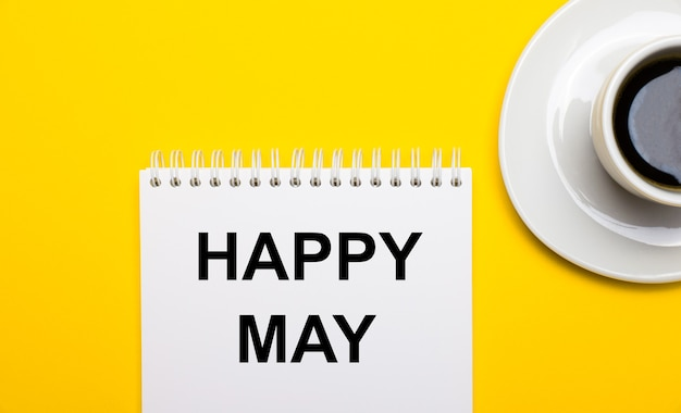 On a bright yellow background, a white cup with coffee and a white notepad with the words happy may