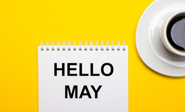 On a bright yellow background, a white cup with coffee and a white notepad with the words hello may