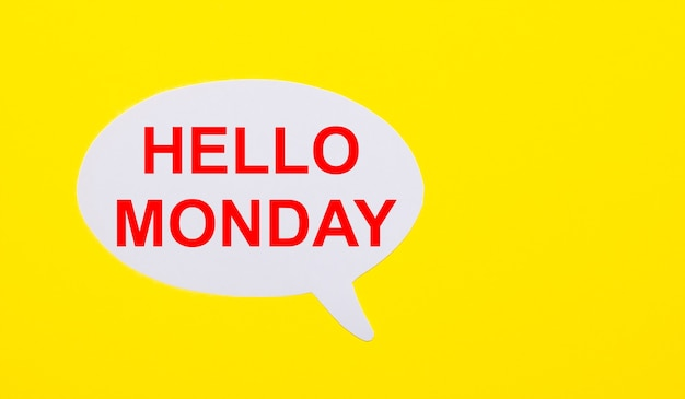 On a bright yellow background, white paper with the words hello monday
