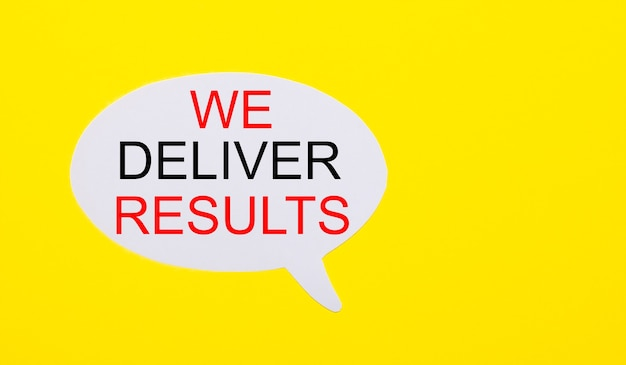 On a bright yellow background, white paper with the words we deliver results