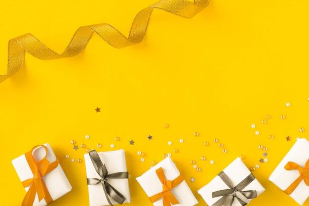 Ярко-желтый фон с золотыми и серебряными элементами подарков и конфетти