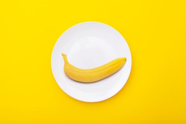 Bright yellow banana on white ceramic plate creative minimal composition