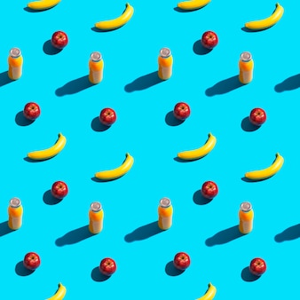 Bright yellow bananas, red apples and bottle of juice on a blue background. seamless pattern.