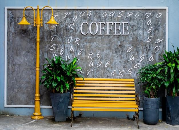 다낭, 베트남, 근접 거리에 회색 콘크리트 벽에 식물이있는 밝은 노란색 벤치와 램프 게시물 및 화분