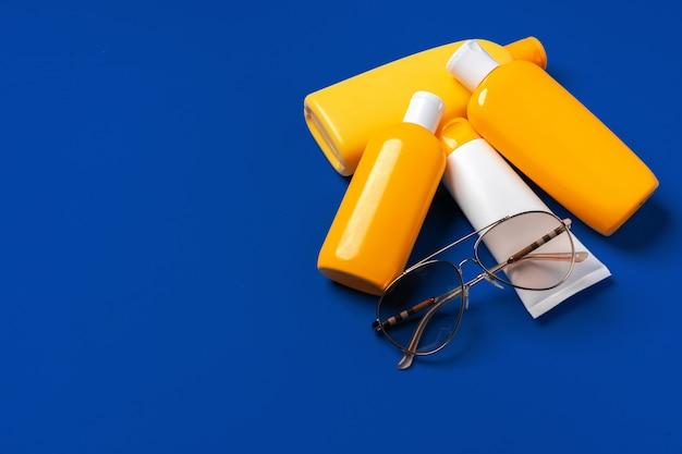 暗い青色の紙の背景に日焼け止め製品の明るい黄色のボトル