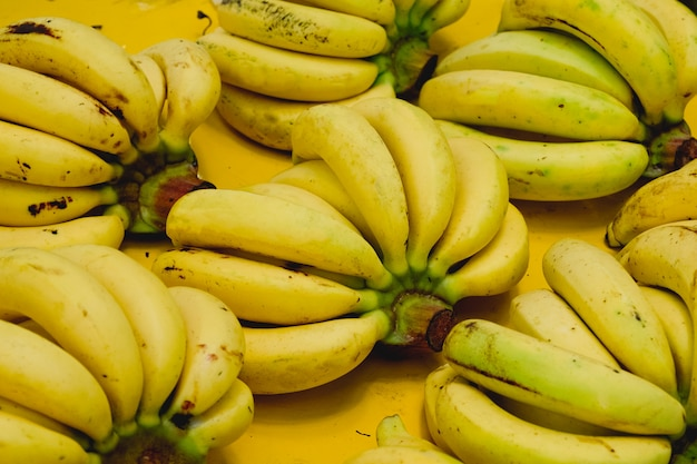 Bright yellow bunch of appetizing ripe bananas background texture