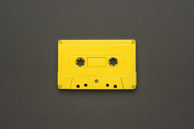A bright yellow cassette with a magnetic tape on a gray background. stylish retro equipment for listening to music. flat lay.