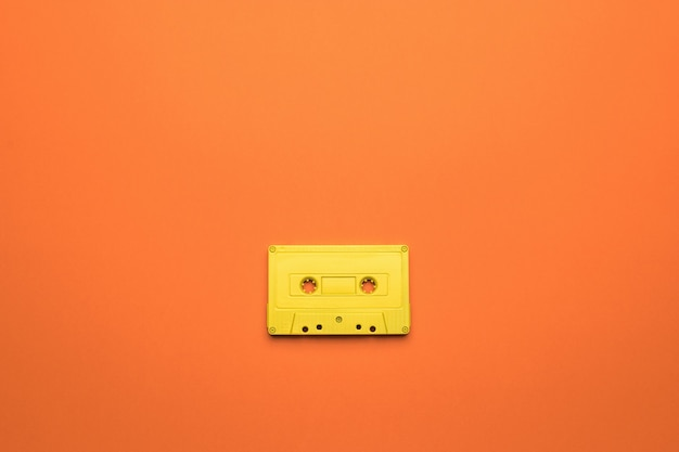 A bright yellow cassette with a magnetic tape on an orange background. stylish retro equipment for listening to music. flat lay.