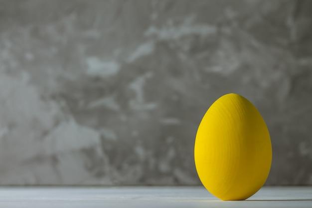 Ярко-желтое пасхальное яйцо, стоящее на белой деревянной поверхности на серой бетонной поверхности