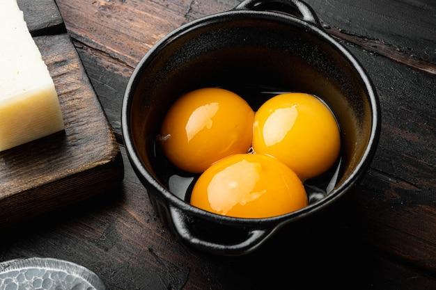 오래된 어두운 나무 테이블에 밝은 노란색 달걀 노른자 세트