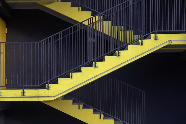 Ярко-желтая внешняя пожарная лестница новой многоуровневой парковки в городе