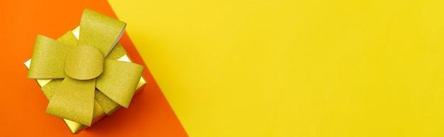 노란색과 주황색 배경에 금색 활과 리본이 있는 밝은 노란색 선물 상자는 축제 배경에 평평하게 놓여 있습니다.