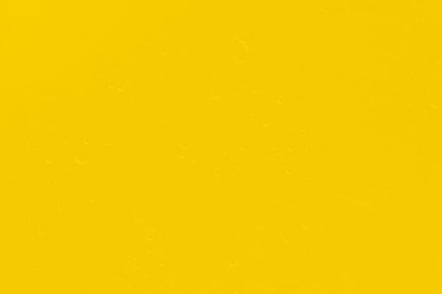 Яркий желтый золотой фон грязный с каплей воды.