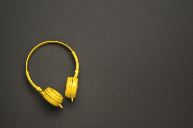 검정색 배경에 밝은 노란색 헤드폰.