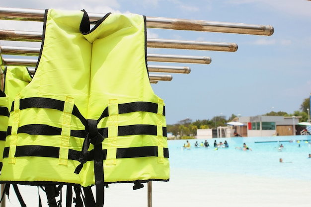 Bright yellow life jacket hangs next to the pool at the waterpark