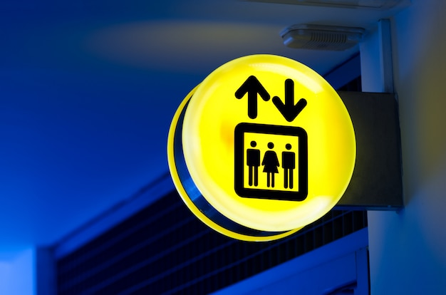 Bright yellow lift or elevator symbol, sign on blue wall background with neon light. copy space